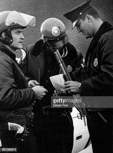 A dismantled shotgun recovered from two juvenile's car is inspected by Denver Patrolmen Robert A Thiede Jr left Lowell F Carlson center and Robert L...