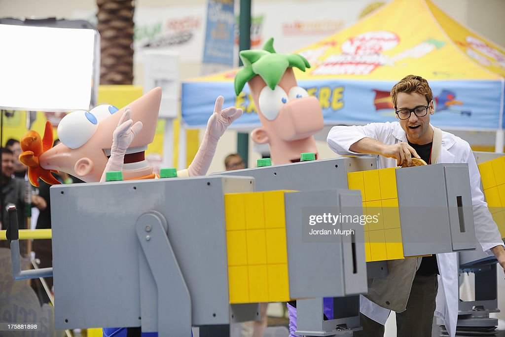 D23 EXPO -Disney Channel unveils Dr. Doofenshmirtz's most wacky '-inator' yet -- 'The Waffle-inator' -- a spectacular 40-foot high interactive game, combining physical and digital worlds -- and rapid-flying waffles -- in an epic showdown to free Agent P from the clutches of Dr. Doofenshmirtz, at Disney's D23 Expo, the ultimate event for Disney fans at the Anaheim Convention Center in Anaheim, California (August 9). 'The Waffle-inator' celebrates the TV crossover special, 'Phineas and Ferb: Mission Marvel,' premiering FRIDAY, AUGUST 16 at 8:00 ET/PT on Disney Channel. Joining the celebration were (Phineas and Ferb or Spider-Man and Iron Man) characters, stars Dan Povenmire (creator/executive producer & 'Dr. Doofenshmirtz'), Swampy Marsh (creator/executive producer & 'Major Monogram'), Vincent Martella ('Phineas'), Alyson Stoner ('Isabella');Marvel Universe stars Drake Bell ('Spider-Man'), Adrian Pasdar ('Iron Man'), Fred Tatasciore ('Hulk') and Travis Willingham ('Thor'). PHINEAS, FERB