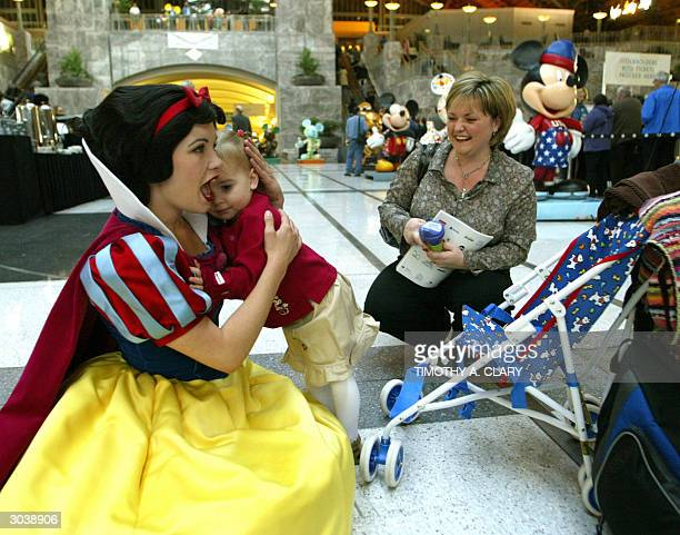 Disney characteer Snow White hugs 2yearold Emma Cooper while her mother looks on before the start of the Walt Disney Company's annual meeting of the...