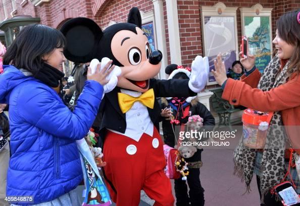 Disney character Mickey Mouse exchange greetings with guests at Tokyo Disneyland in Urayasu suburban Tokyo on January 1 2014 Tokyo Disney Resort...