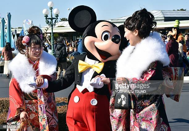 Disney character Mickey Mouse greets 20yearold women wearing kimonos during their 'ComingofAge Day' celebration at Tokyo Disneyland in Urayasu...