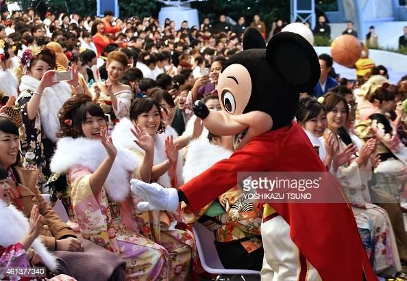 Disney character Mickey Mouse greets 20yearold women wearing kimonos during their 'ComingofAge Day' celebration at Tokyo Disneyland in Urayasu...