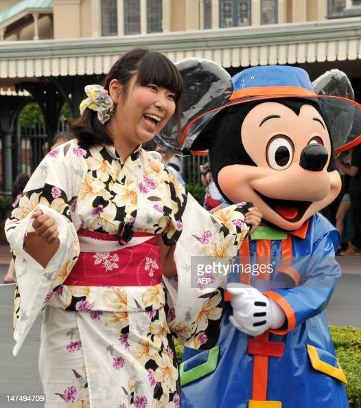 Disney character Mickey Mouse greets a young woman wearing a 'yukata' or summerstyle kimono at Tokyo Disneyland in Urayasu suburban Tokyo on July 1...