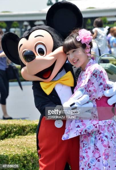 Disney character Mickey Mouse greets a young woman wearing a 'yukata' or summerstyle kimono at Tokyo Disneyland in Urayasu in suburban Tokyo on July...