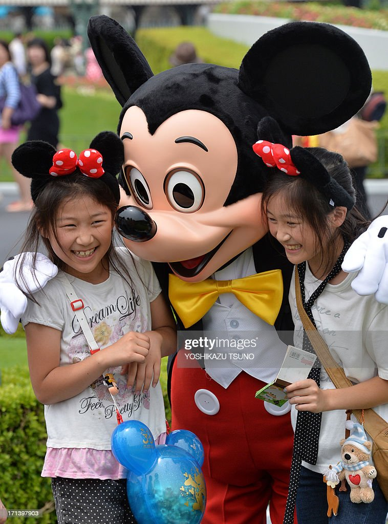 Disney character Mickey Mouse greets two girls at the Tokyo Disneyland in Urayasu, suburban Tokyo on June 24, 2013 as the special parade of the 'Tanabata' or Star Festival started at the Disney theme park through July 7. Tokyo Disneyland celebrated its 30th anniversary this April and Tokyo Disney resort, combined Tokyo Disneyland and Toyko DisneySea, marked a record high of 27.5 million visitors in fiscal 2012. AFP PHOTO / Yoshikazu TSUNO