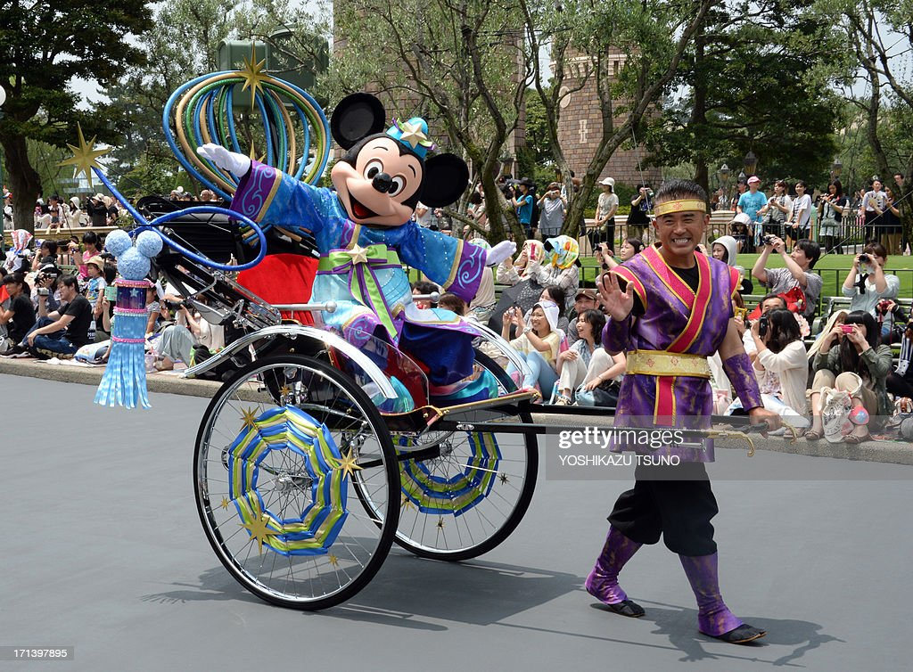 Disney character Mickey Mouse, who represents Altair the Cowherd, waves to spectators from rickshaw to celebrate 'Tanabata' or the Star Festival during the special parade held through July 7 at the Tokyo Disneyland in Urayasu, suburban Tokyo on June 24, 2013. In Japanese legend the two lovers Altair and Vega, who are separated by the Milky Way on most days of the year, meet just once a year on July 7. AFP PHOTO / Yoshikazu TSUNO