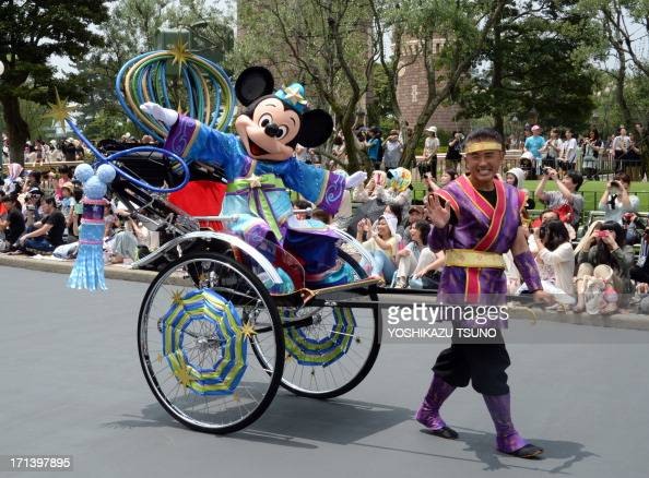 Disney character Mickey Mouse who represents Altair the Cowherd waves to spectators from rickshaw to celebrate 'Tanabata' or the Star Festival during...