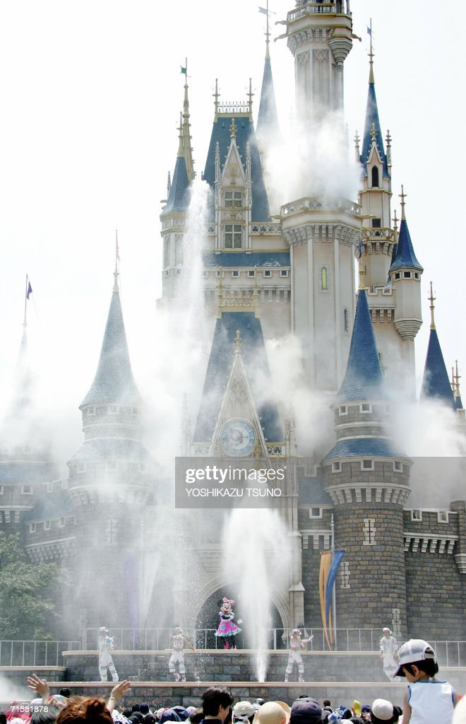 Disney character Minnie Mouse and dancers perform as water splashes up outside Cinderella's castle to cool down the guests during the new summer promotional event 'Cool the Heat' at Tokyo Disneyland in Urayasu, suburban Tokyo, 04 August 2006. The event took place as Tokyo temperatures climbed near 35 degrees Celsius.
