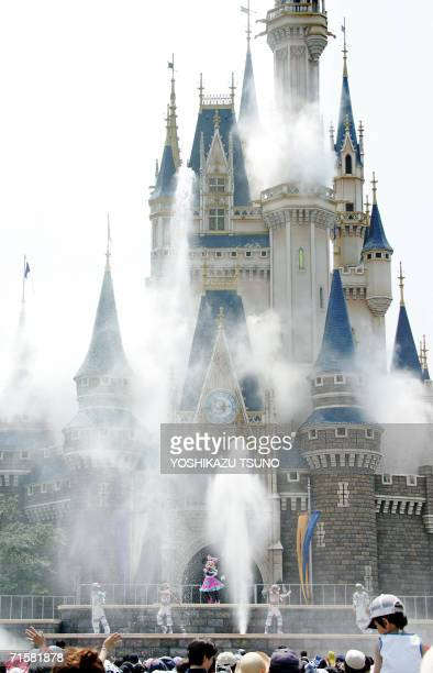Disney character Minnie Mouse and dancers perform as water splashes up outside Cinderella's castle to cool down the guests during the new summer...
