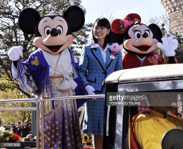 Disney characters Mickey and Minnie Mouse dressed in traditional Japanese kimonos and accompanied by Tokyo Disney Resort ambassador Tomoko Baba wave...