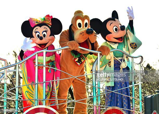Disney characters Mickey and Minnie Mouse dressed in traditional Japanese kimonos accompanied by Pluto wave to greet guests from a float during the...