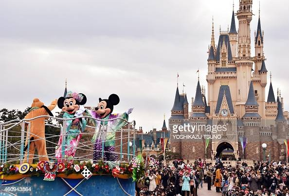 Disney characters Mickey and Minnie Mouse dressed in traditional Japanese kimonos and Pluto wave to greet guests from a float during the theme park's...