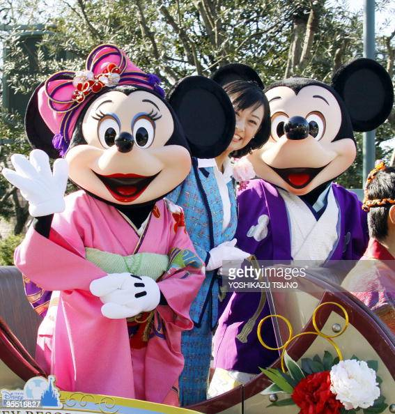 Disney characters Mickey and Minnie Mouse dressed in traditional Japanese kimonos and accompanied by Tokyo Disney Resort ambassador Yuna Omiya wave...