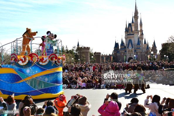 Disney characters Mickey dressed in a traditional Japanese kimono accompanied by Pluto waves to greet guests from a float during the theme park's...
