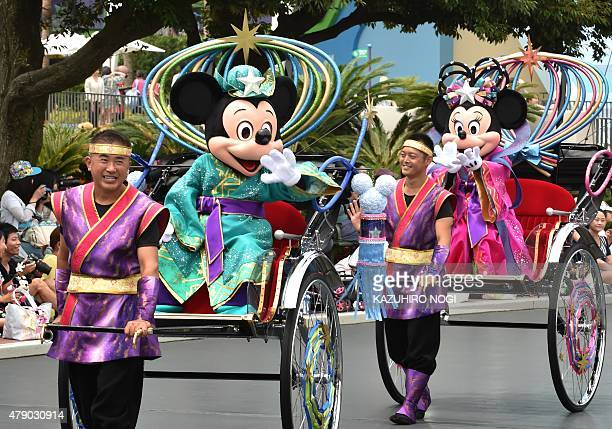 Disney characters Mickey Mouse and Minnie Mouse dressed in 'Tanabata' or the Star Festival costumes wave from rickshaws as they greet guests along...