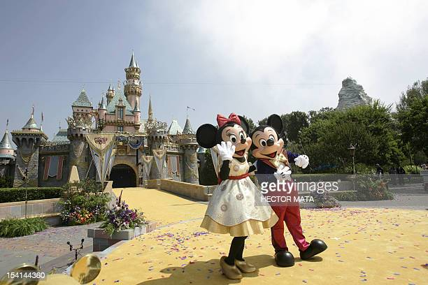 Disney characters Mickey Mouse and Minnie wave to a crowd of people in front the Sleeping Beauty Castle during the 50th anniversary of the opening of...