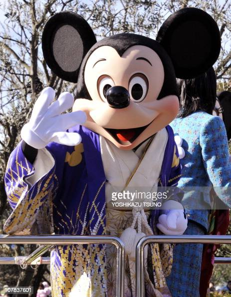 Disney characters Mickey Mouse dressed in traditional Japanese kimono waves to greet guests during the theme park's annual New Year's Day parade at...