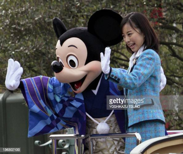Disney characters Mickey Mouse dressed in traditional Japanese kimono and Tokyo Disney Resort ambassador Eriko Yokota wave to greet guests from a...