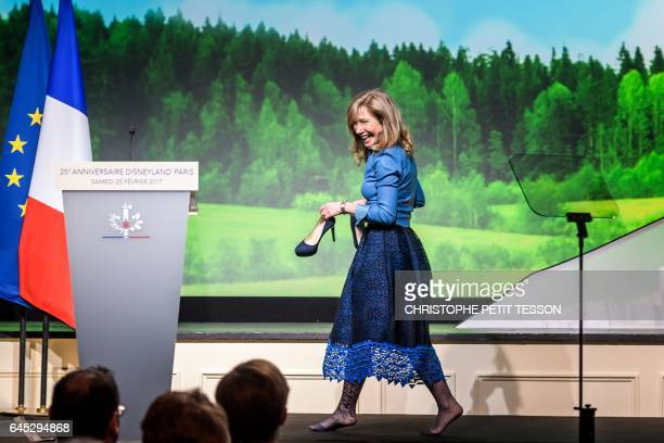 Disneyland Paris president Catherine Powell holds her shoes as she arrives on stage to deliver a speech during a ceremony marking the 25th...