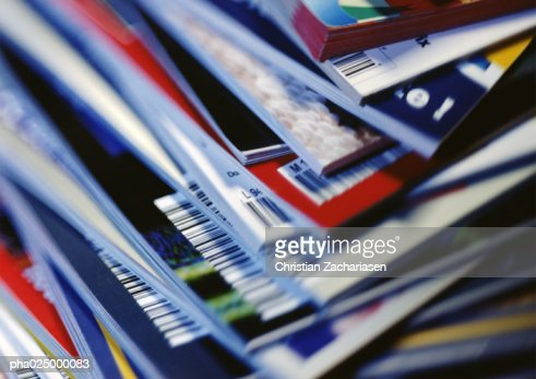 Disorderly stack of magazines, extreme close-up on corners with barcodes, full frame