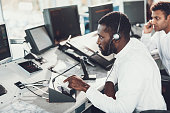 Center of dispatching maintenance. Top angle side on portrait of afro-american male specialist speaking on microphone while working on navigation control board