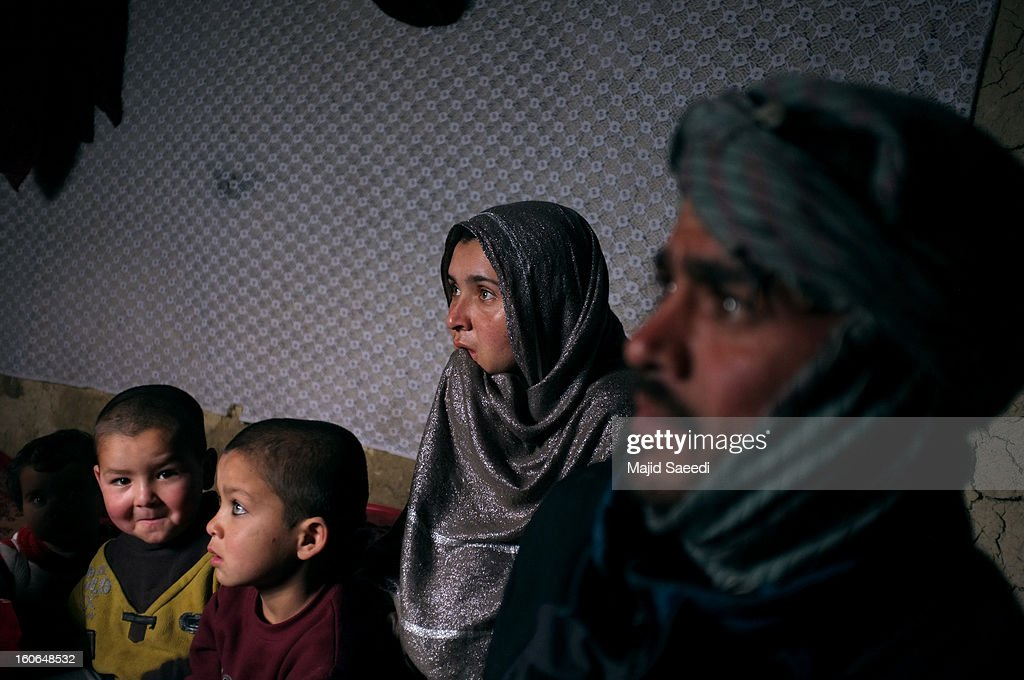 A displaced Afghan family inside their temporary home after receiving a donation at Chamand babrak Camp, on February 3, 2013 in Kabul, Afghanistan. According to the UN refugee agency, Afghanistan's internally displaced population has reached half a million, although the actual figure is believed to be much higher.