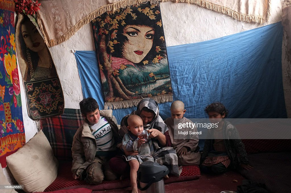 A displaced Afghan family sit around their mother as she helps a child drink at Chamand babrak Camp, on February 3, 2013 in Kabul, Afghanistan. According to the UN refugee agency, Afghanistan's internally displaced population has reached half a million, although the actual figure is believed to be much higher.