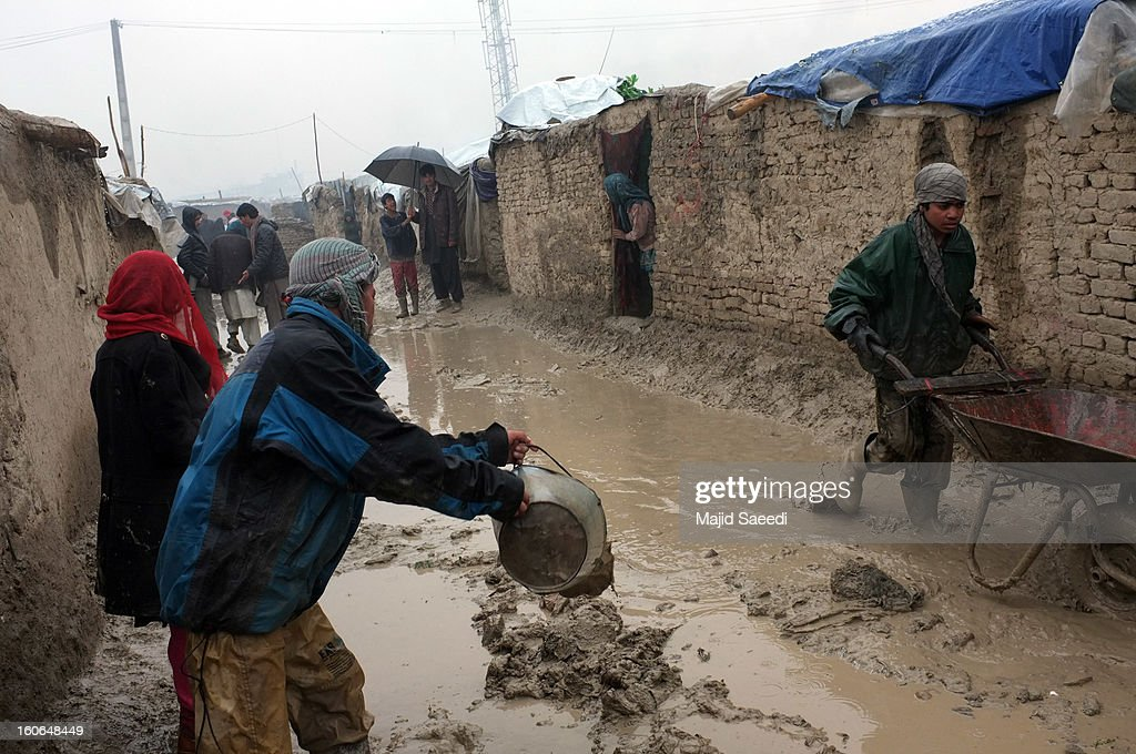 Displaced Afghans clear effluent in the heavy rain from outside their temporary homes at Chamand babrak Camp, on February 3, 2013 in Kabul, Afghanistan. According to the UN refugee agency, Afghanistan's internally displaced population has reached half a million, although the actual figure is believed to be much higher.