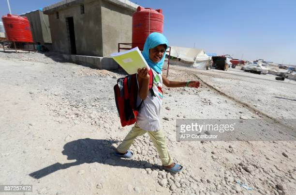 TOPSHOT A displaced child from the Islamic State group's Syrian stronghold of Raqa walks to attend the first day of the new school year at a camp for...