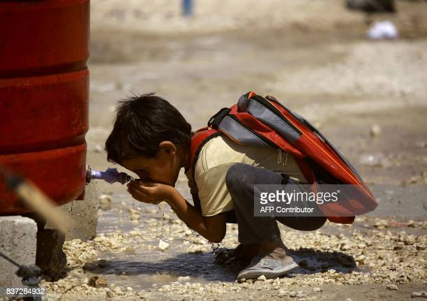 TOPSHOT A displaced child from the Islamic State group's Syrian stronghold of Raqa drinks water as he head to attend the first day of the new school...