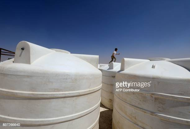 TOPSHOT A displaced child from the Islamic State group's Syrian stronghold of Raqa runs along to top of water containers at a camp in Ain Issa on...