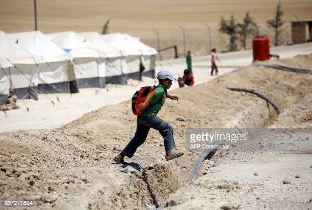 A displaced child from the Islamic State group's Syrian stronghold of Raqa jumps over a ditch on his way to attend a class at a camp for internally...