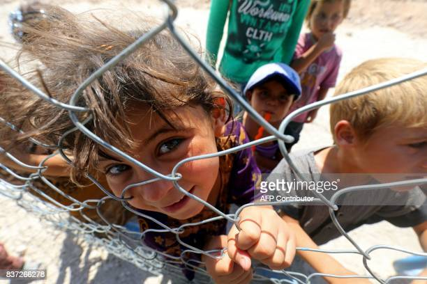 TOPSHOT Displaced children from the Islamic State group's Syrian stronghold of Raqa pose for a photo behind a fence at a camp in Ain Issa on August...