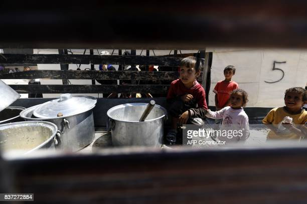 Displaced children from the Islamic State group's Syrian stronghold of Raqa wait to receive food at a camp for internally displaced people in Ain...