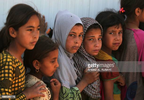 TOPSHOT Displaced children stand in line to get food at the Hammam alAlil camp for internally displaced people south of Mosul on May 25 as government...