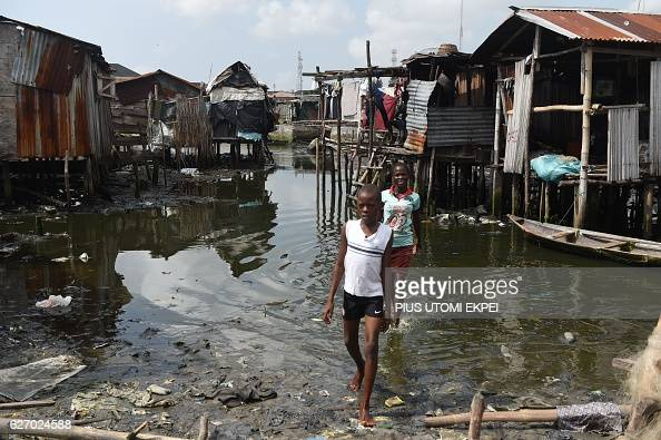 Displaced children walk past shallow water away from their shanty home partly demolished by the authorities at Otodo Gbame waterfront fishing...