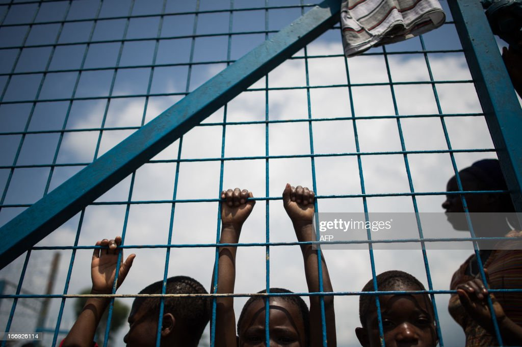 Displaced Congolese children stand against the gate of a religious organisation on the outskirts of Goma in the east of the Democratic Republic of the Congo on November 25, 2012. Over half a million people have been displaced in eastern Congo since the outbreak of the M23 rebellion. Diplomatic efforts continued on November 25 to resolve the crisis in eastern DR Congo, with an M23 rebel leader expected to hold further talks with President Joseph Kabila as the African Union called on the rebels to pull out from Goma. AFP PHOTO / PHIL MOORE