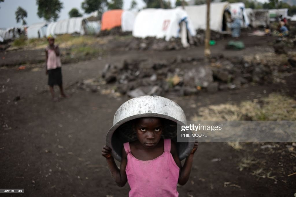 A displaced Congolese childs carries a basin on July 14 2014 at the Bulengo camp for internally displaced persons 20 kms west of Goma in the east of...