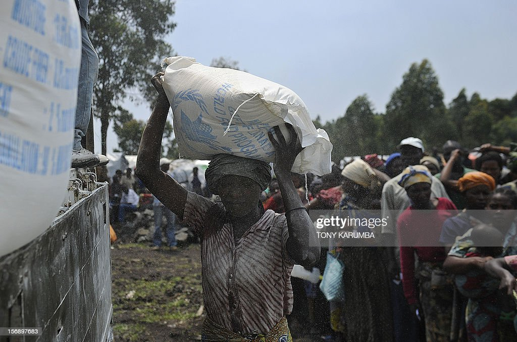 A displaced Congolese woman volunteers to offload sack of maize-flour during a food aid distribution exercise conducted by humanitarian agencies at a camp for the internally displaced in Mugunga, on November 24, 2012. Thousands of people have been displace in sporadic fighting between M23 rebel outfit against government forces in easten D.R. Congo's north-Kivu region after M23 seized control of the regional capital Goma. Regional leaders called on DR Congo rebel group M23 Saturday to end hostilities and relinquish a key eastern town it seized in an advance that has sparked fears of a wider conflict. The meeting of heads of state went forward without a key player -- Rwandan President Paul Kagame, whose country the United Nations accuses of backing the rebels -- and wrapped up quickly. AFP PHOTO/Tony KARUMBA