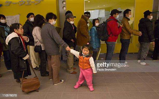 Displaced earthquake victims line up for a meal as hundreds pack a evacuation center on March 22 2011 in Kesennuma Miyagi Japan Eleven days after the...