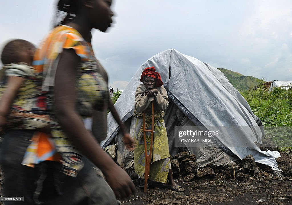 A displaced elderly Congolese woman stands outside her makeshift shelter during a food aid distribution exercise conducted by humanitarian agencies at a camp for the internally displaced in Mugunga, on November 24, 2012. Thousands of people have been displace in sporadic fighting between M23 rebel outfit against government forces in easten D.R. Congo's north-Kivu region after M23 seized control of the regional capital Goma. Regional leaders called on DR Congo rebel group M23 Saturday to end hostilities and relinquish a key eastern town it seized in an advance that has sparked fears of a wider conflict. The meeting of heads of state went forward without a key player -- Rwandan President Paul Kagame, whose country the United Nations accuses of backing the rebels -- and wrapped up quickly. AFP PHOTO/Tony KARUMBA