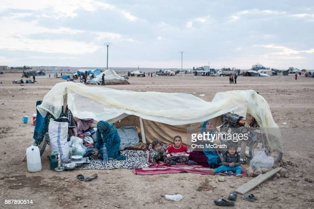 A displaced family sits under a makeshift shelter after newly arriving at a camp for internally displaced people on October 29 2017 in Ain Issa Syria...