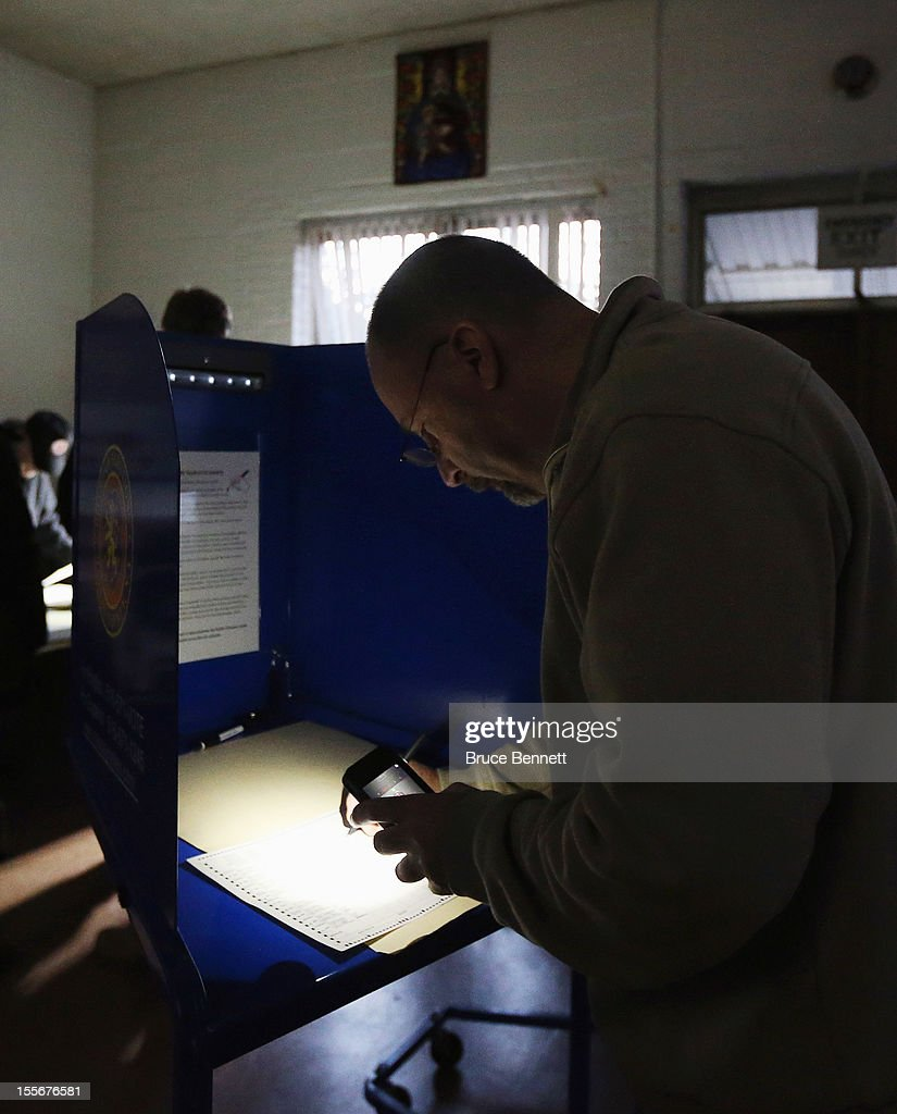 Displaced from his assigned polling location, Larry Zassman of Oceanside marks his ballot via cell phone light at the generator powered First United Methodist Church on November 6, 2012 in Oceanside, New York. The Many voters in New York and New Jersey are voting at alternate locations in the presidential election due to disruption from Superstorm Sandy.