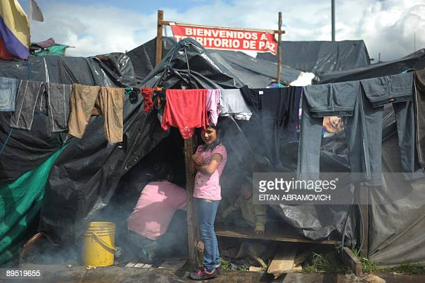 A displaced girl stands outside a makeshift tent at the Parque Tercer Milenio downtown Bogota on July 30 2009 More than 800 people gathered at the...