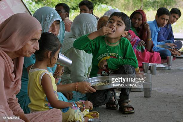 Displaced Indian villagers who fled firing along the IndiaPakistan border eat a meal at a camp in Ghagwal about 40 kms from Jammu on October 11 2014...