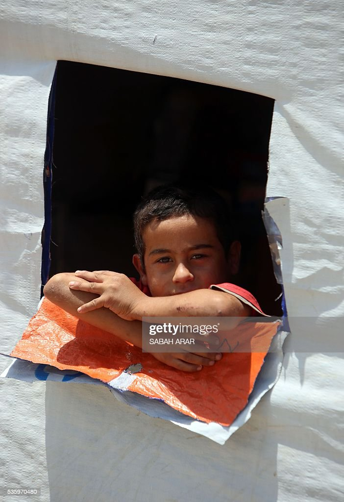A displaced Iraqi boy looks out from the window of a tent on May 31, 2016 at the Alexanzan camp in the Dora neighbourhood on the southern outskirts of Baghdad where he is taking shelter with his family after they were displaced from the Jbeil, a village near the embattled Iraqi city of Fallujah due to clashes between pro-government forces and the Islamic State (IS) group. Only a few hundred families have managed to slip out of the Fallujah area ahead of the assault on the city, with an estimated 50,000 civilians still trapped inside, sparking fears the jihadists could try to use them as human shields. ARAR