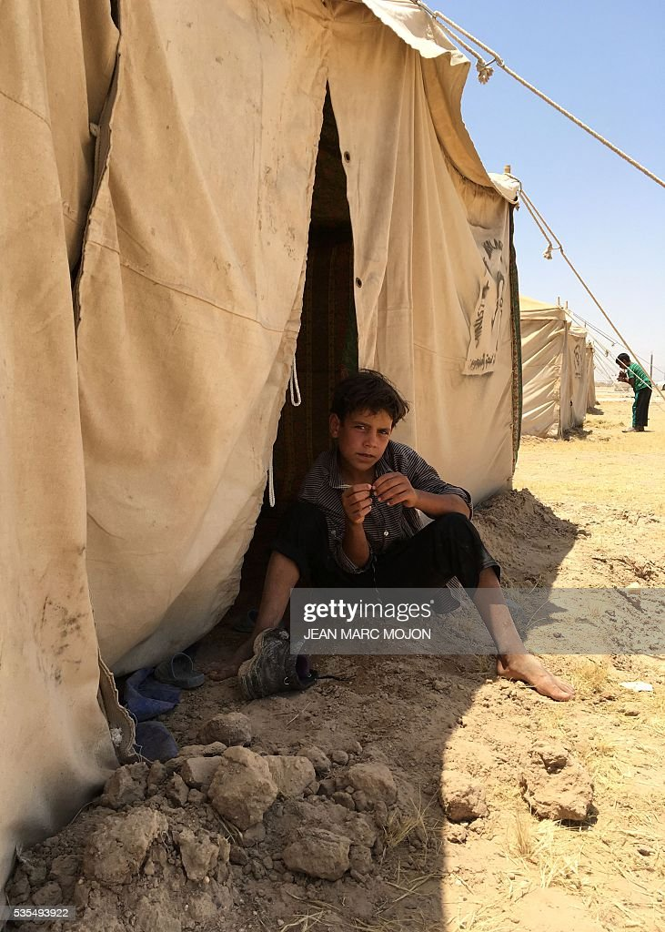 A displaced Iraqi boy sits on May 29, 2016 under the shade of a tent at a newly-opened camp in the government-held town of Amriyat al-Fallujah 50 kilometres (30 miles) southwest of Baghdad, which was set up to shelter people fleeing violence around the city of Fallujah. The Norwegian Refugee Council, which runs the camp in Amriyat al-Fallujah, says around 3,000 people have managed to flee the area and reach displacement camps since Iraqi forces launched an operation against the Islamic State a week ago. The biggest wave of arrivals so far was Saturday night and included mostly exhausted and hungry women and children. / AFP / Jean Marc MOJON
