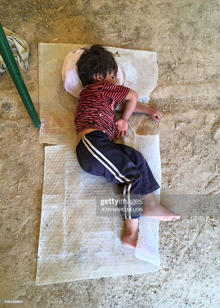 A displaced Iraqi boy sleeps on May 29, 2016 inside a tent at a newly-opened camp in the government-held town of Amriyat al-Fallujah 50 kilometres (30 miles) southwest of Baghdad, which was set up to shelter people fleeing violence around the city of Fallujah. The Norwegian Refugee Council, which runs the camp in Amriyat al-Fallujah, says around 3,000 people have managed to flee the area and reach displacement camps since Iraqi forces launched an operation against the Islamic State a week ago. The biggest wave of arrivals so far was Saturday night and included mostly exhausted and hungry women and children. / AFP / Jean Marc MOJON
