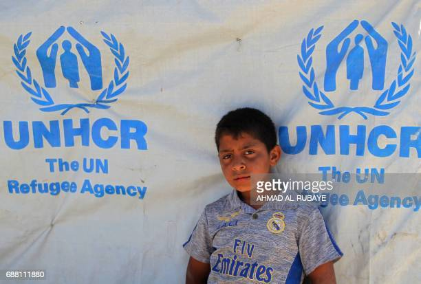 A displaced Iraqi boy stands in front of a tent at the Hammam alAlil camp for internally displaced people south of Mosul on May 25 as government...