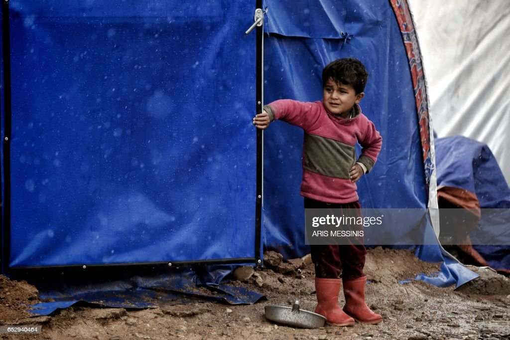 A displaced Iraqi boy stands under the rain at the Hamam al-Alil camp on March 13, 2017, during the government forces ongoing offensive to retake the western parts of the city from Islamic State (IS) group fighters. /
